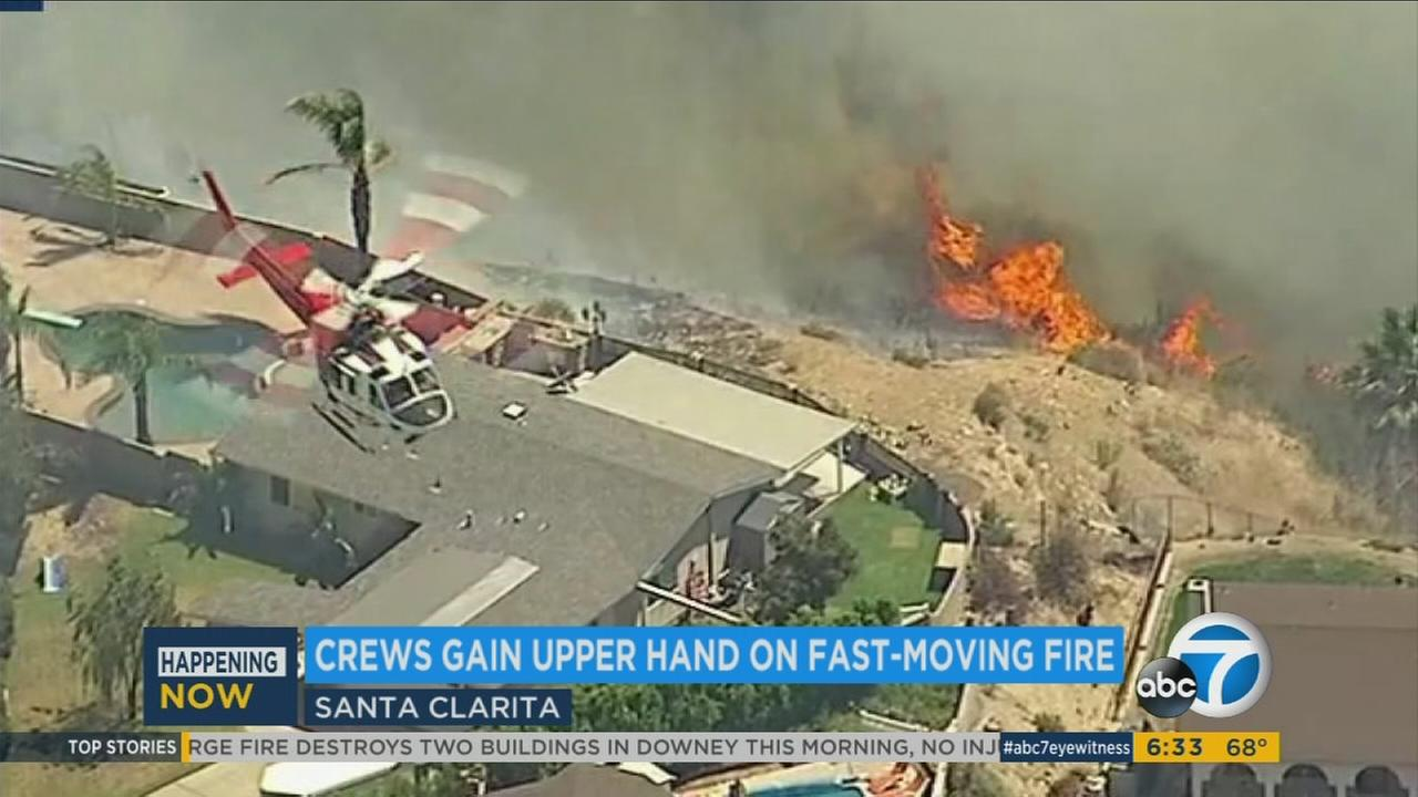 Firefighters continue to battle a fast-moving brush fire in the Santa Clarita area that burned more than 870 acres Sunday.