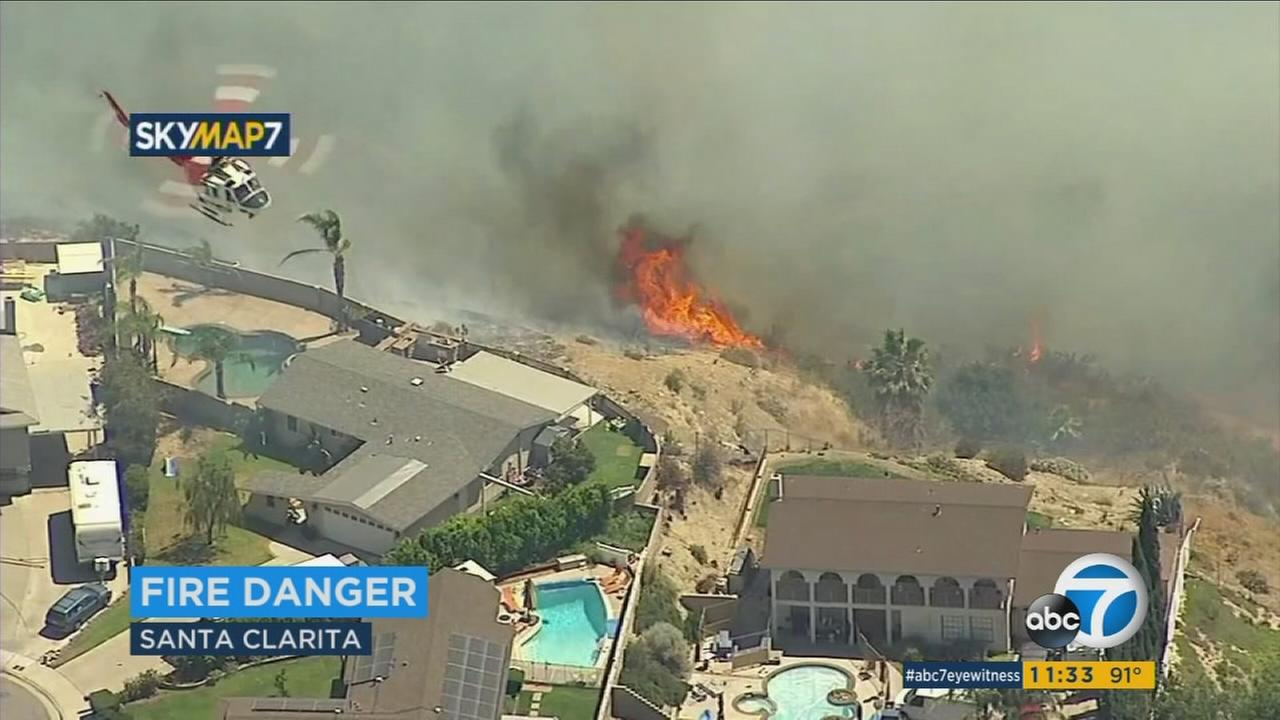 Firefighters are working for a second day to put out an 870-acre brush fire in Santa Clarita, but excessive heat and high winds are making containment of the blaze a tricky task.