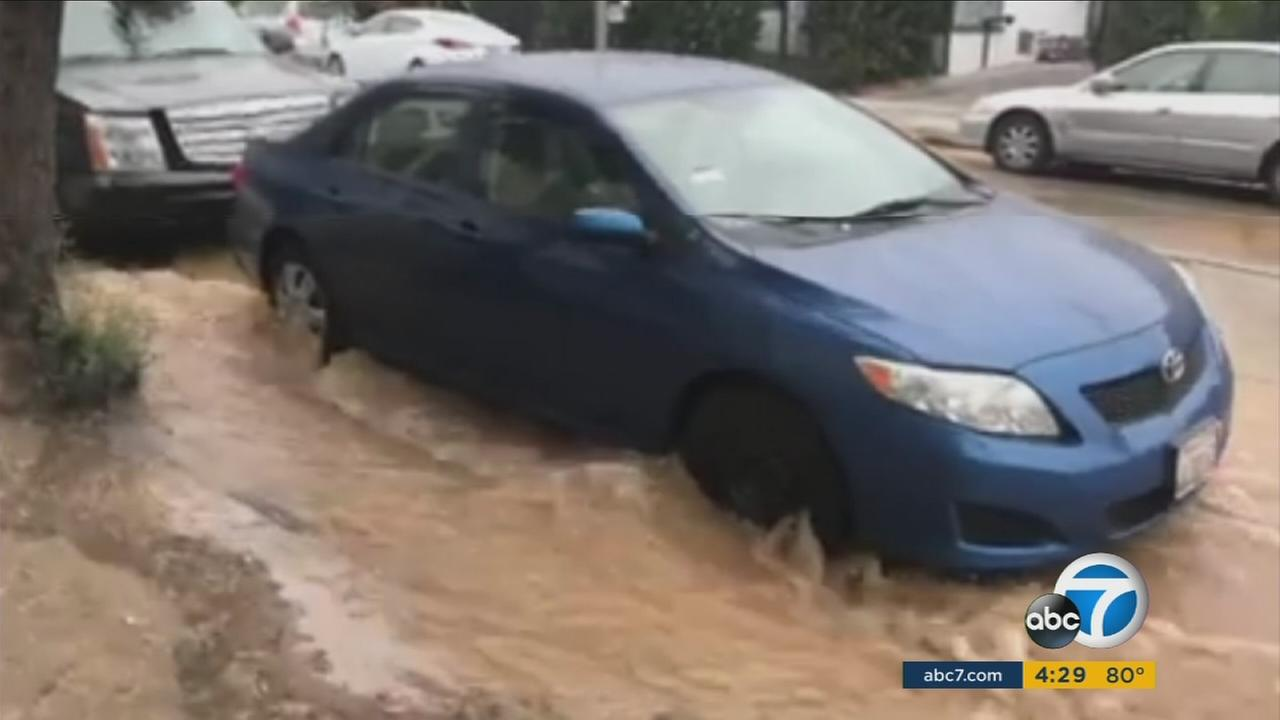 Huge streams of muddy water gushed over Hollywood streets after a 12-inch water main burst Sunday.