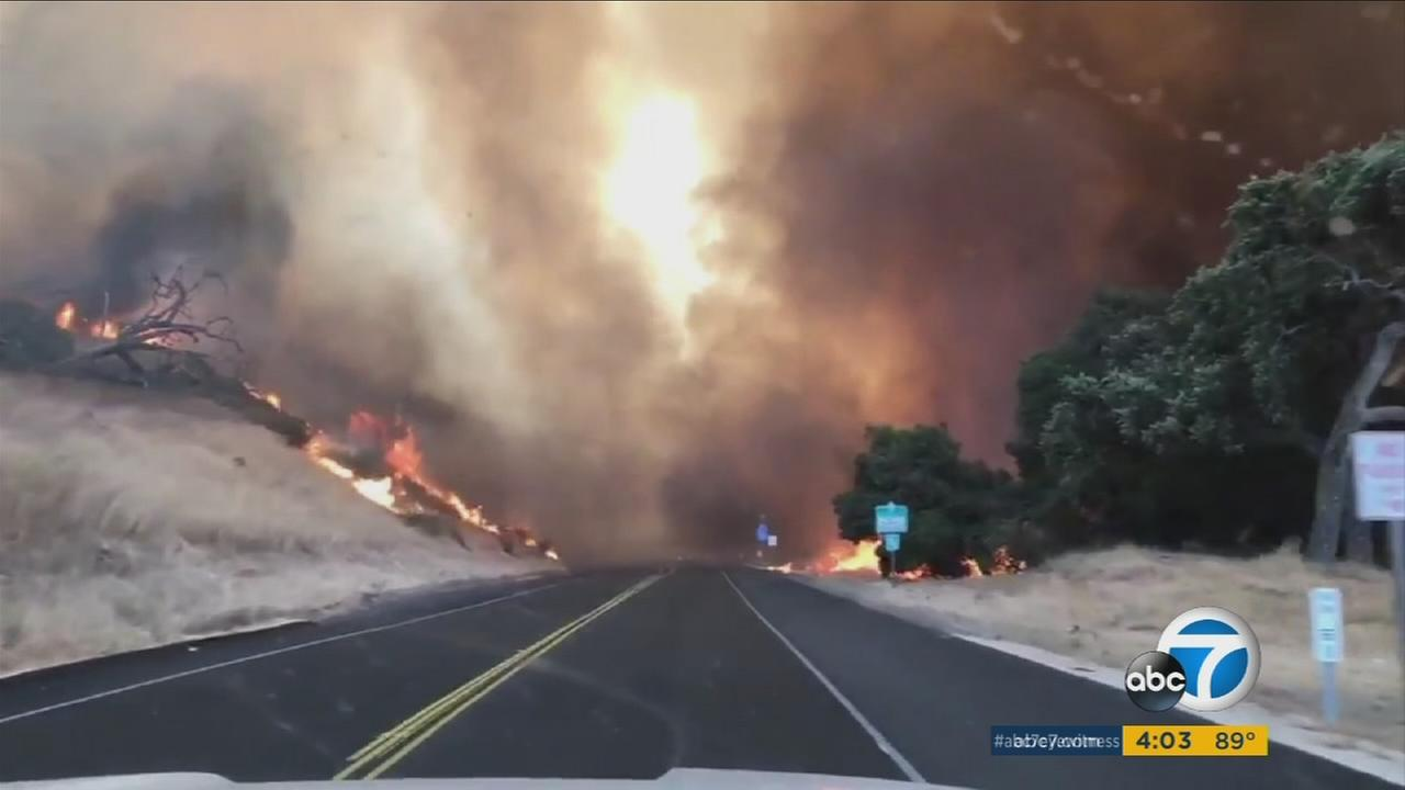 Flames seen on both sides of a highway in Santa Barbara County as the Whittier Fire continues to burn thousands of acres on Sunday, July 9, 2017.