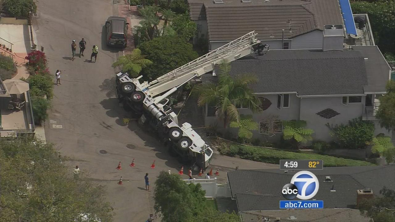 A crane topples over onto the roof of a Laguna Beach home on Friday, July 25, 2014.