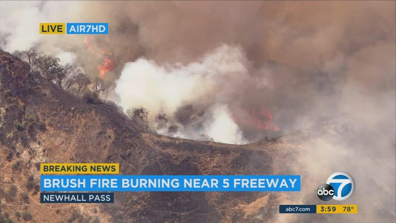 One person was taken into custody for allegedly starting a brush fire in the Newhall Pass by setting off a smoke bomb in a paintball park, officials said.
