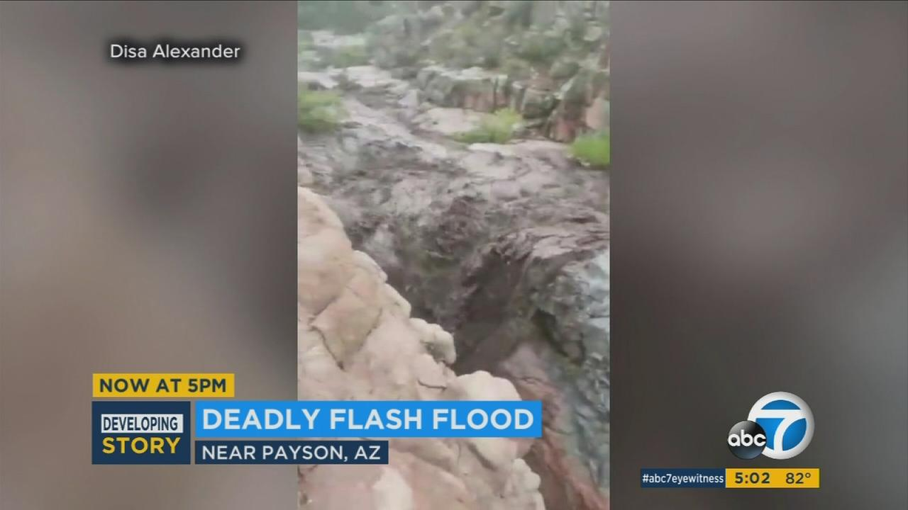 A flash flood barreled through a popular Arizona swimming hole where more than a hundred people were taking refuge from summer heat.