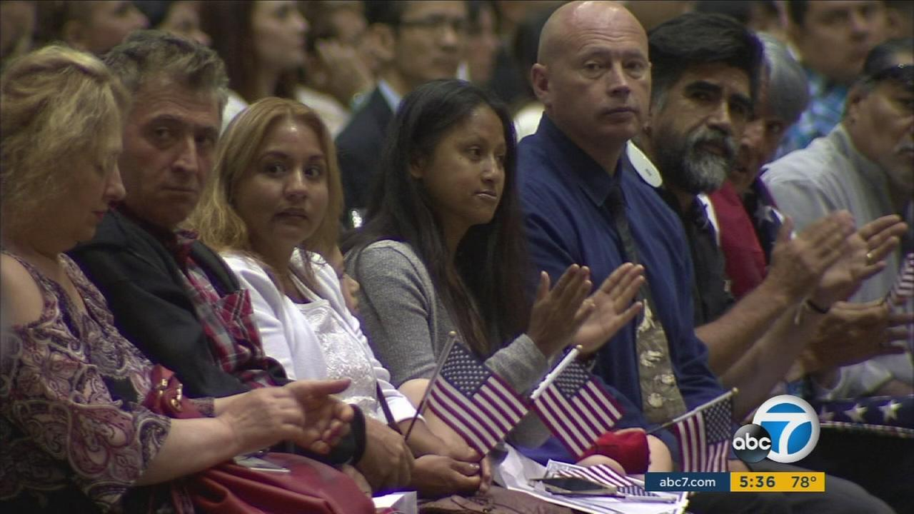 New American citizens wave American flags during their citizenship ceremony in downtown Los Angeles on Tuesday, July 18, 2017.