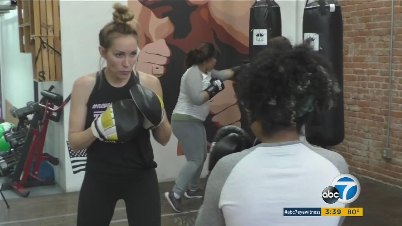 A teenage girl is shown boxing with the owner of Too Pretty Brand boxing.