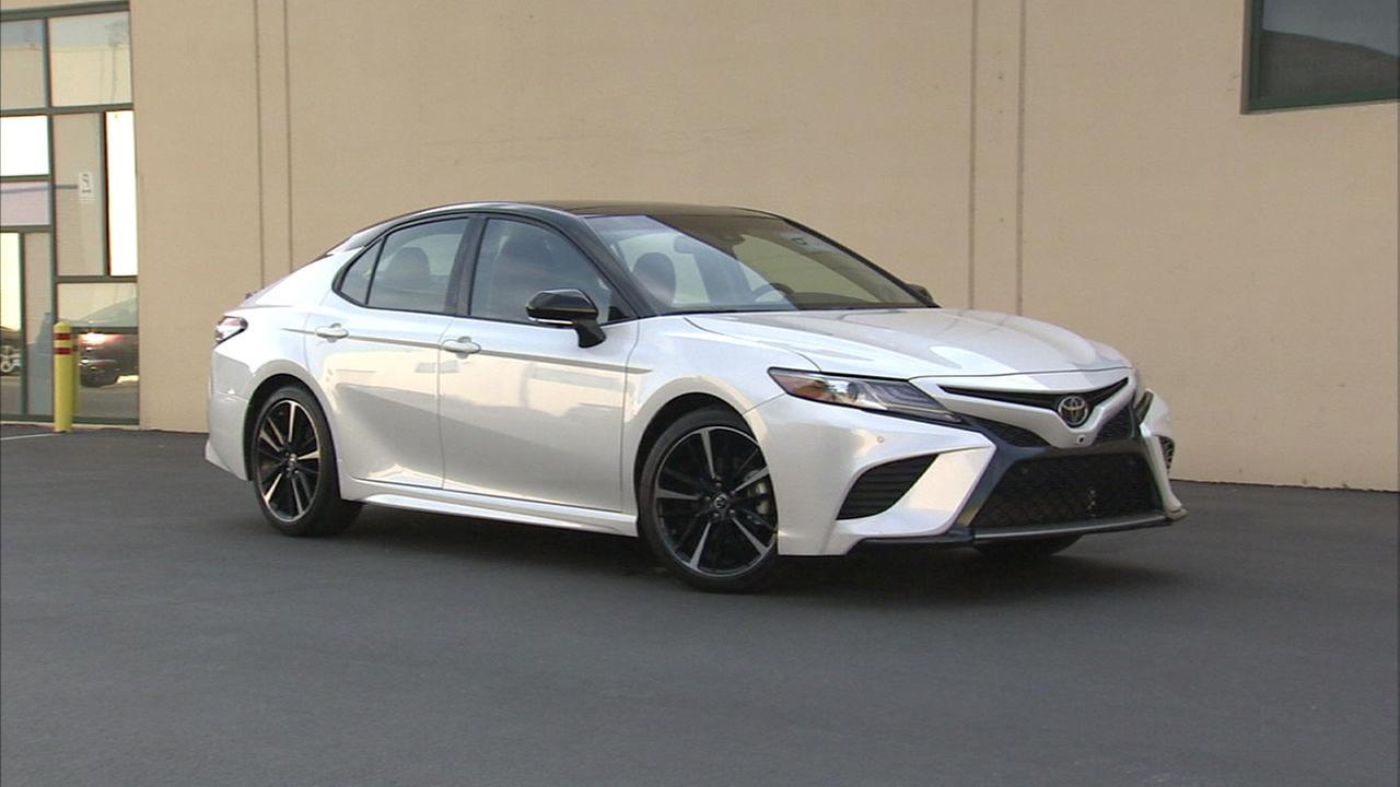 A white Toyota Camry is shown.