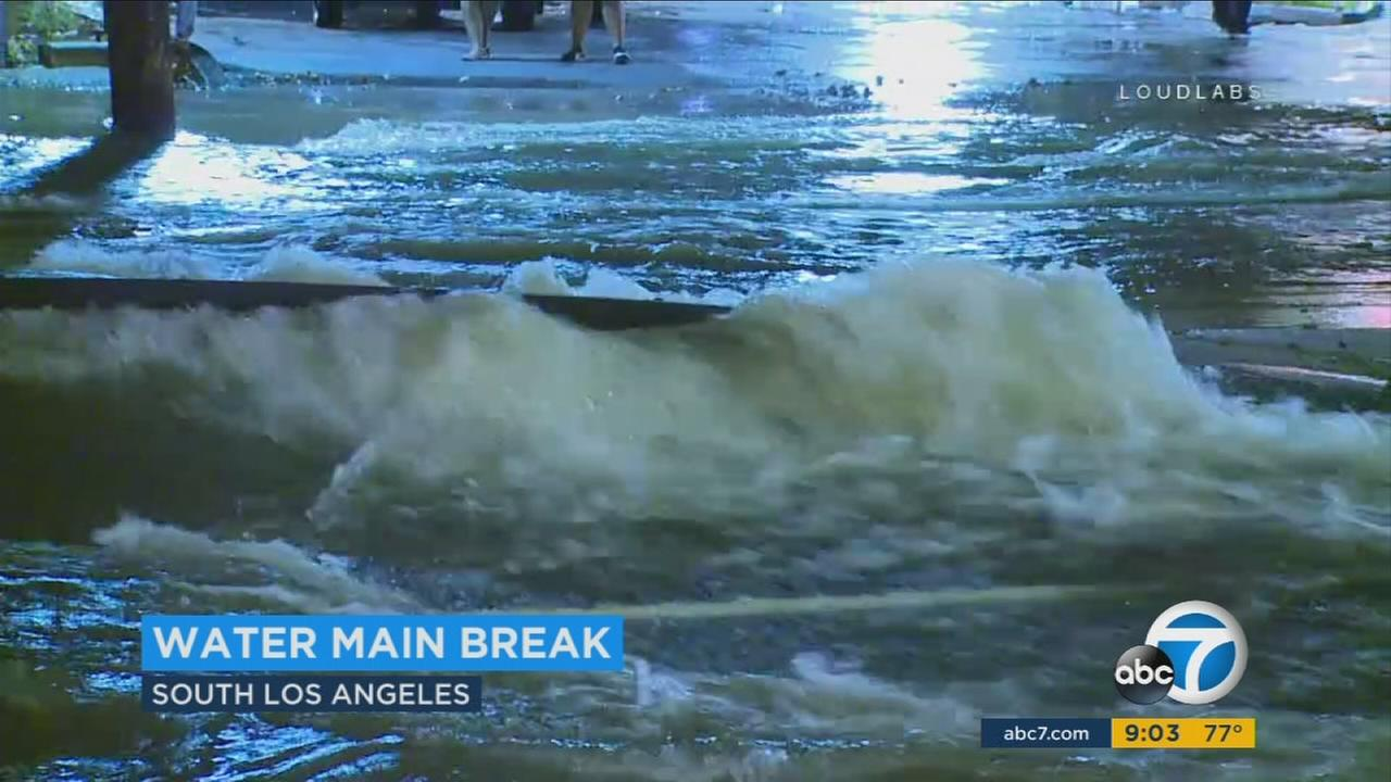 Water gushes into the street after a water main ruptured in South Los Angeles on Sunday, July 23, 2017.