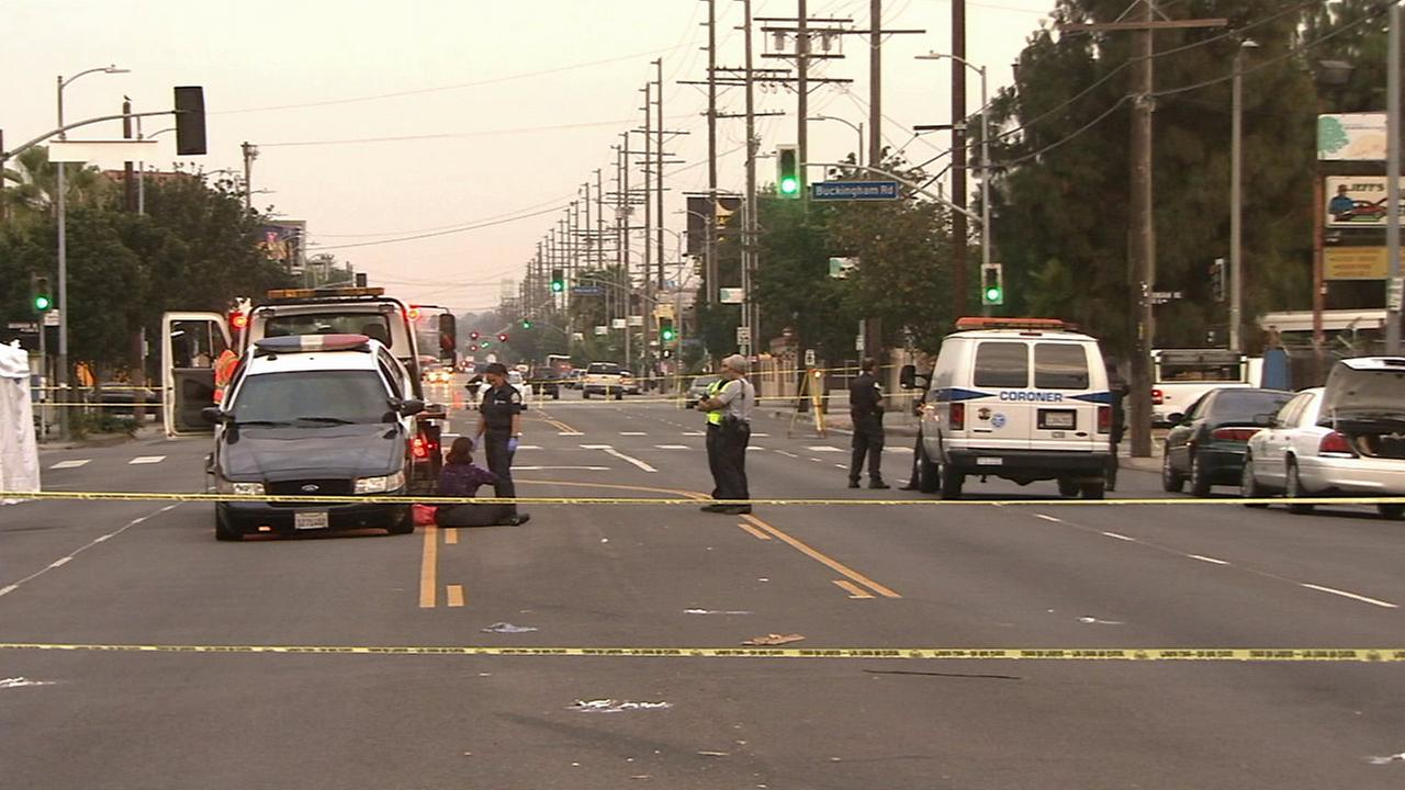 Authorities investigate the scene where a man lying naked in the road was hit and killed by an LAPD patrol car on Sunday, July 27, 2014.