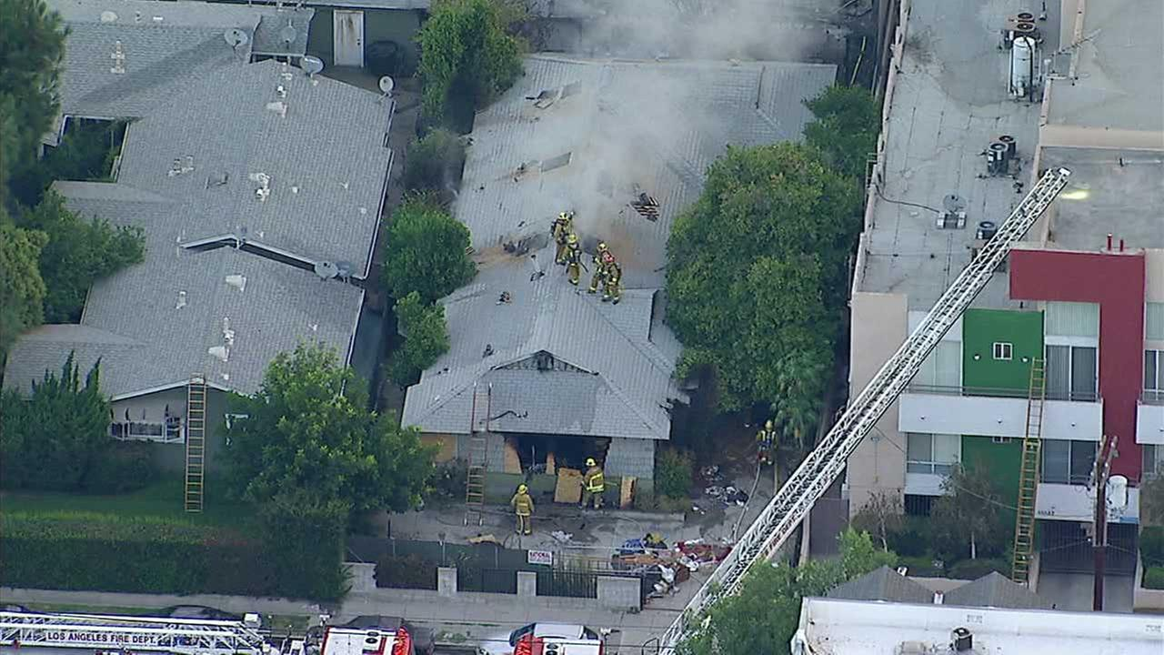 Firefighters are seen working to extinguish flames along a row of duplexes in North Hollywood on Wednesday, Aug. 2, 2017.