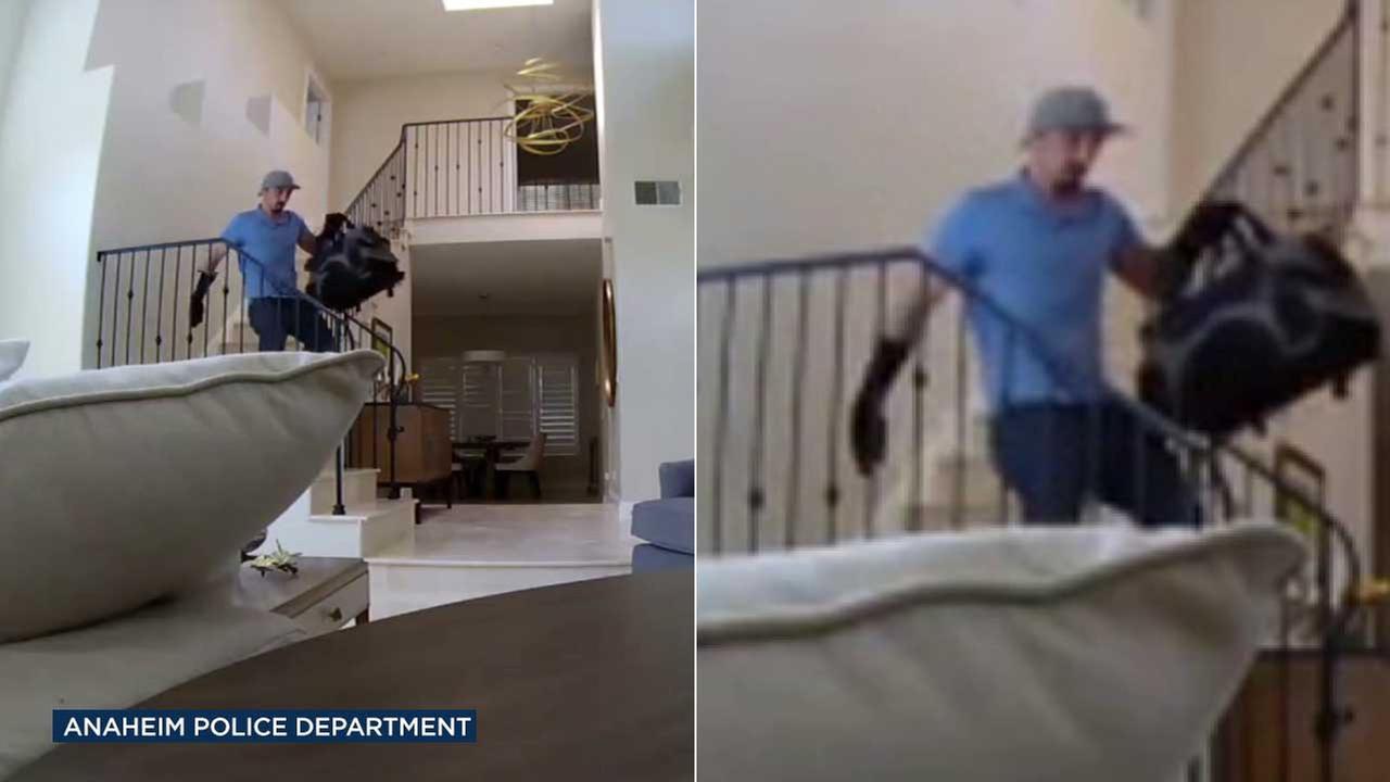 A burglary suspect is seen holding a duffel bag full of stolen goods after ransacking an Anaheim home in June.