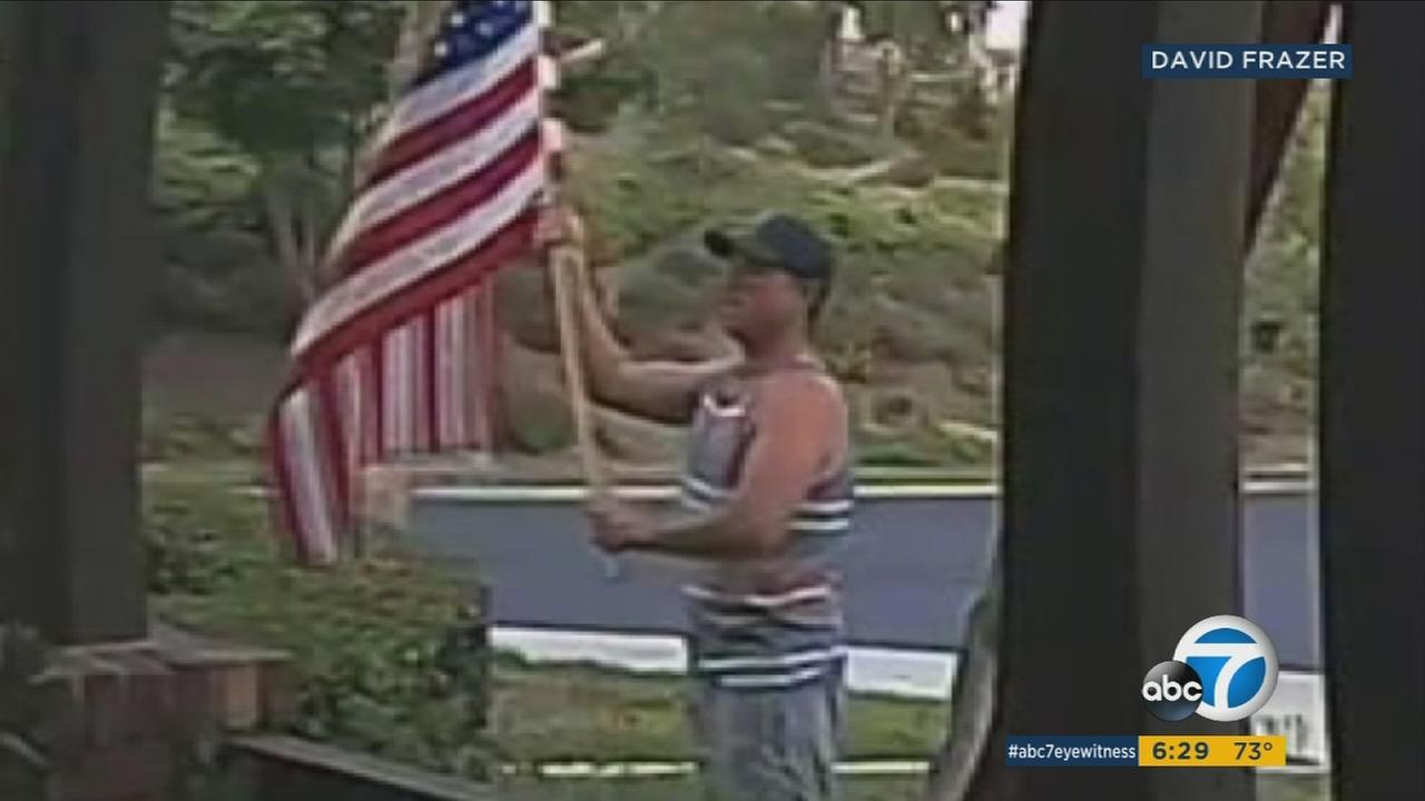 Surveillance video shows a man putting a flag that fell from the side of a home back on display as a kind gesture.
