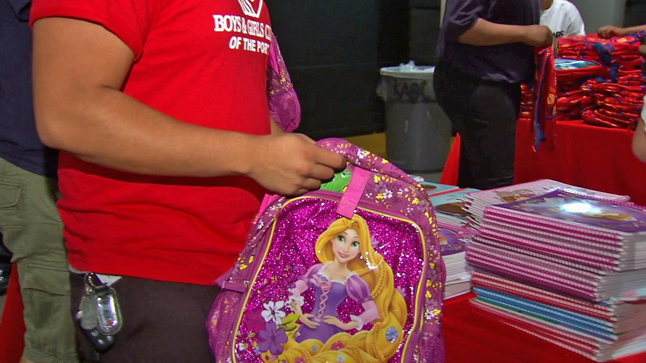 A member of the Boys and Girls Club fills a backpack with school supplies during an event Thursday, July 31, 2014.
