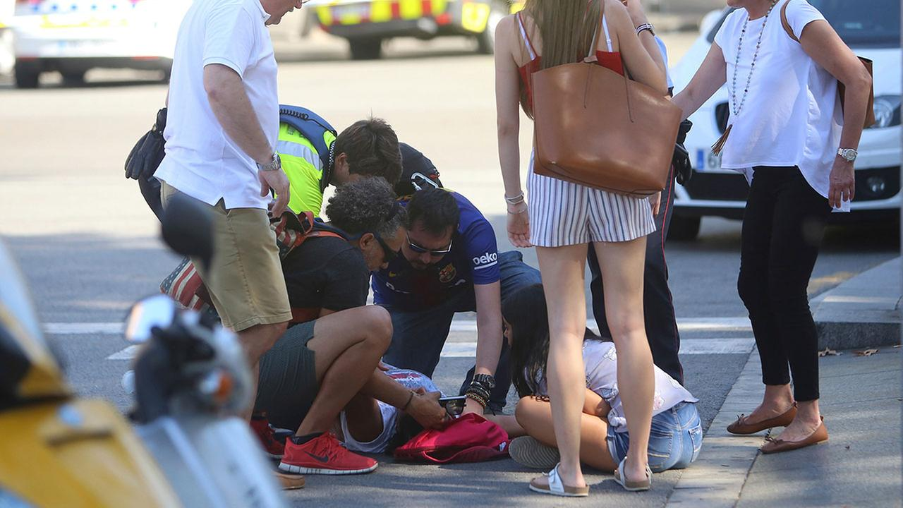 An injured person is treated in Barcelona, Spain, Thursday, Aug. 17, 2017 after a white van jumped the sidewalk in the historic Las Ramblas district.