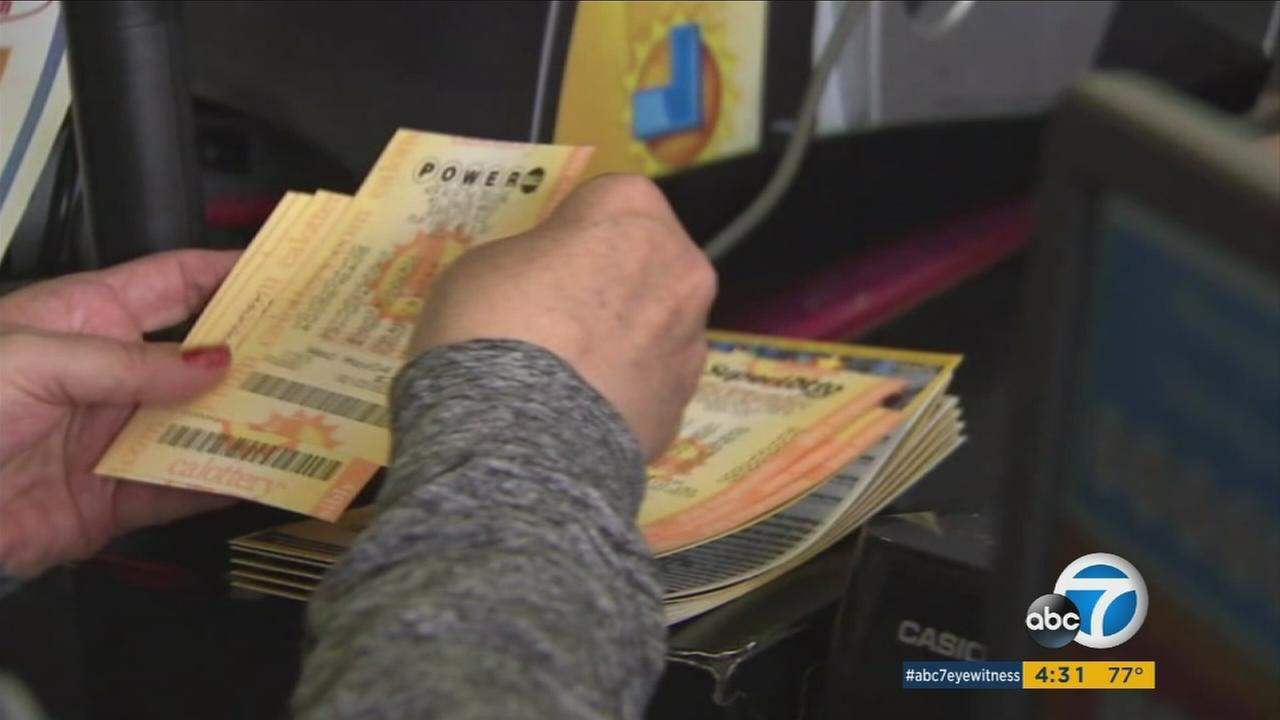 A person is shown handling Powerball tickets.
