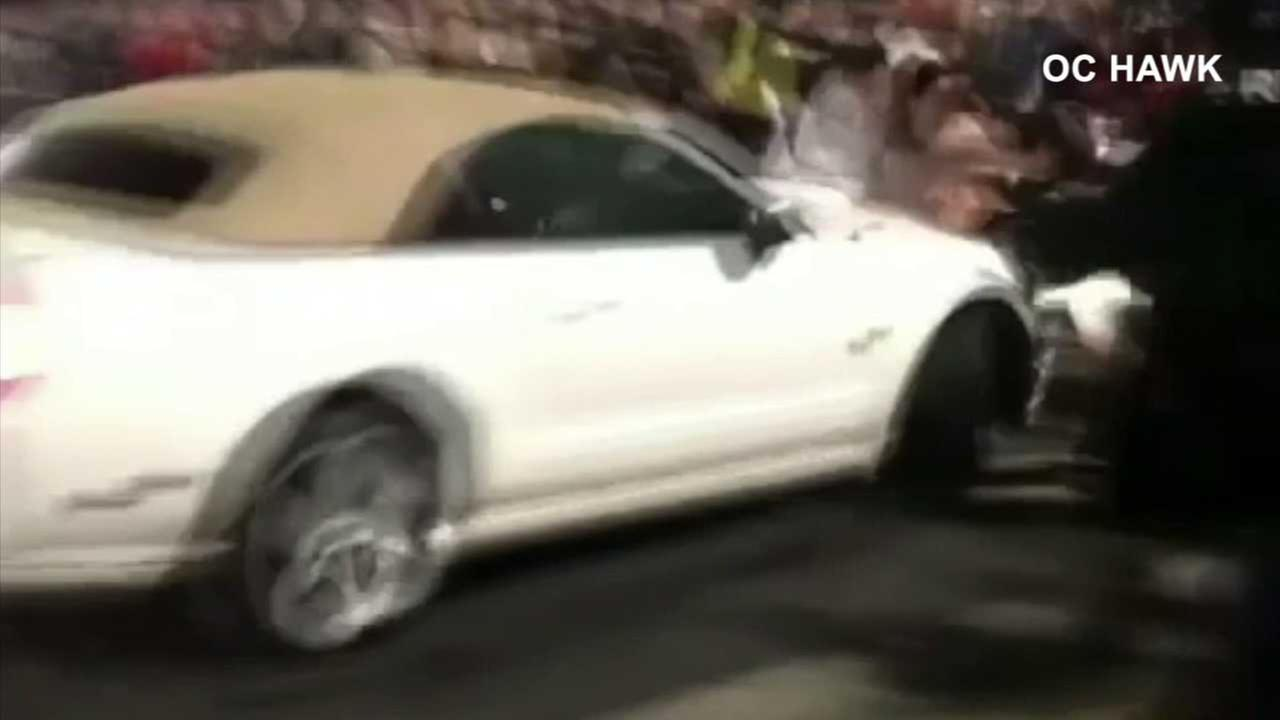 A white Mustang is seen crashing into a crowd of spectators in Bellflower on Saturday, Aug. 19, 2017.