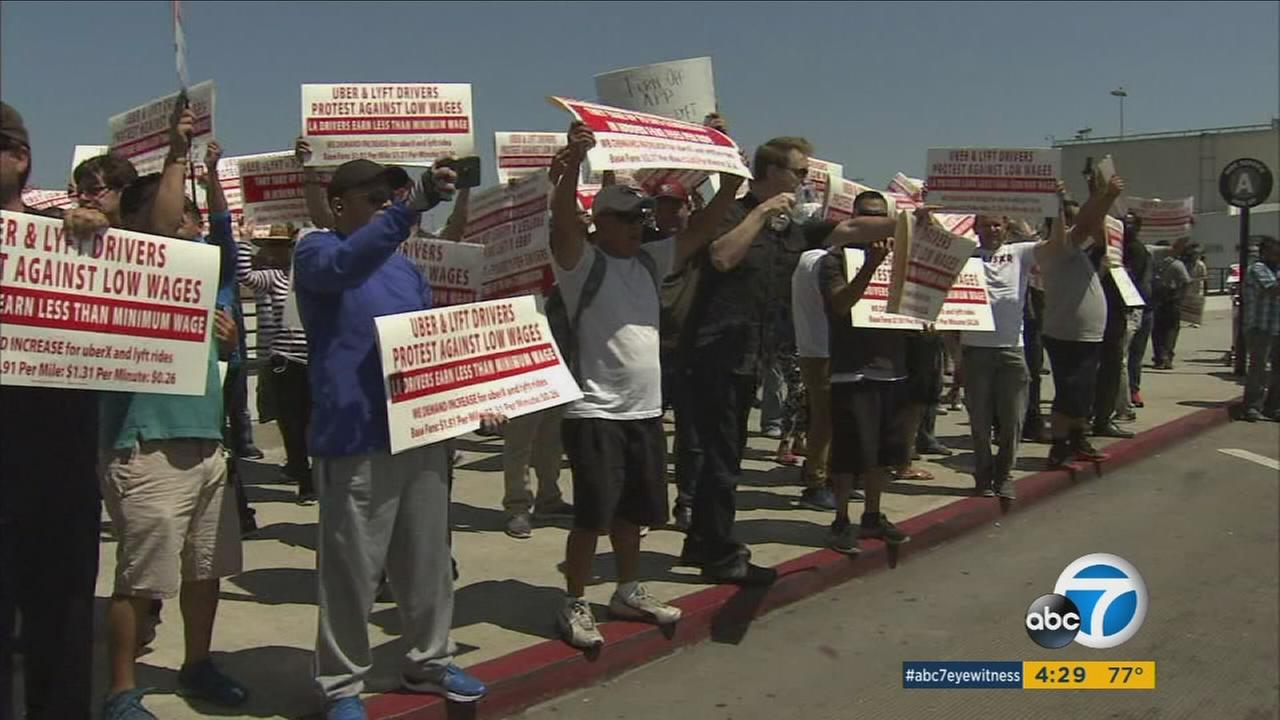 Dozens of protesters packed the sidewalk outside of a busy terminal at the Los Angeles International Airport Tuesday, Aug. 22, 2017.