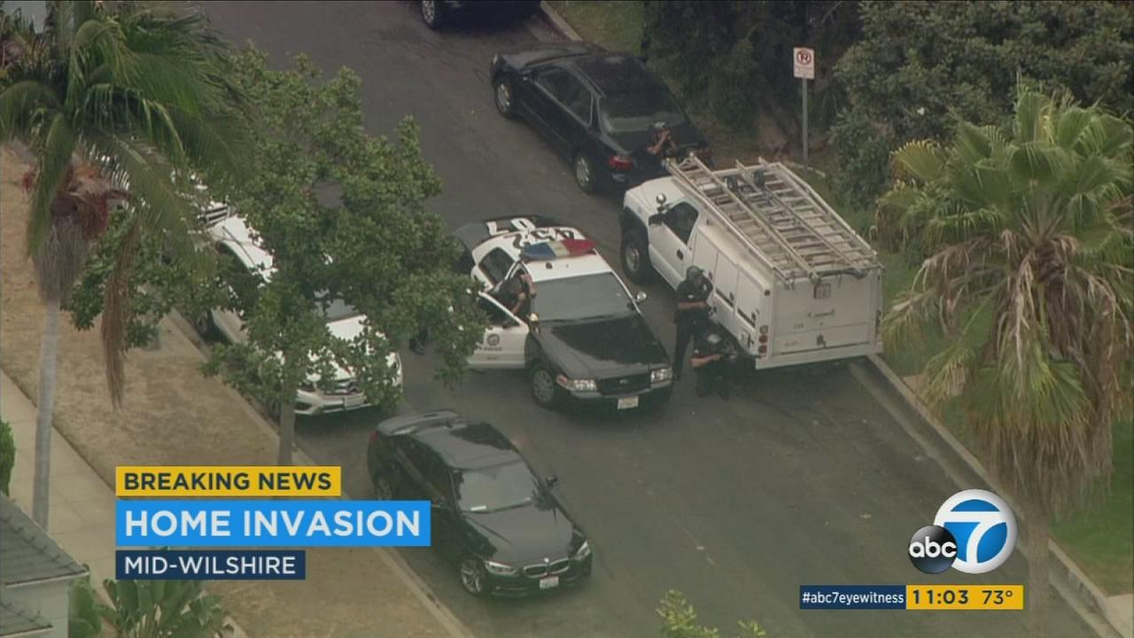 Law enforcement officials investigate the scene of a violent home invasion in the Mid-Wilshire area of Los Angeles on Wednesday, Aug. 23, 2017.