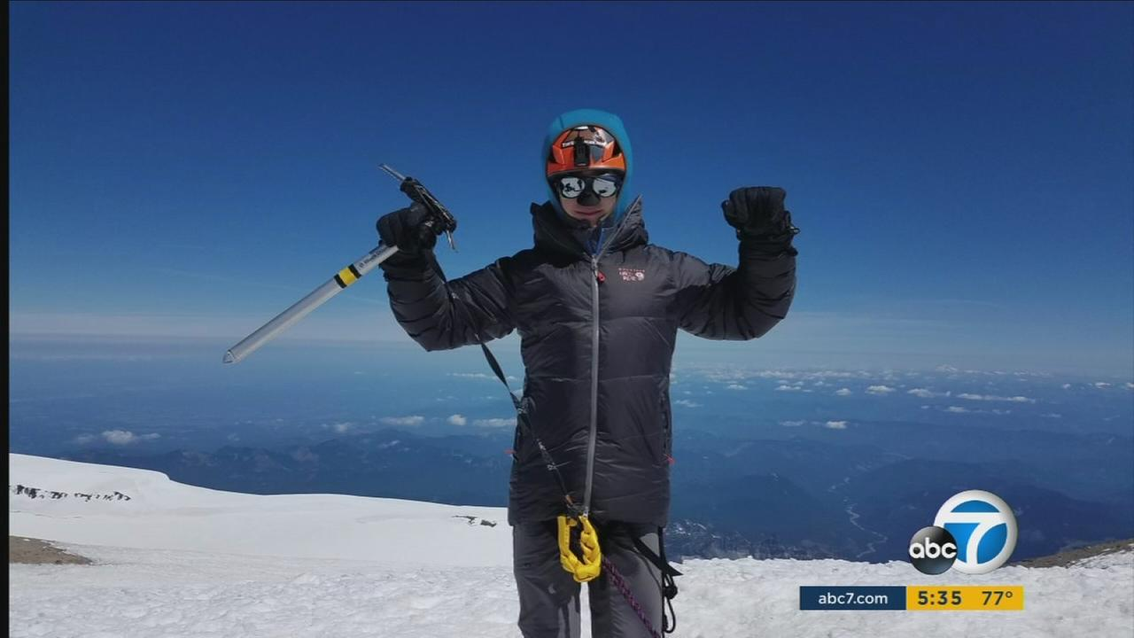 Tyler Armstrong, 13, is shown at the top of a mountain after one of his many adventures.