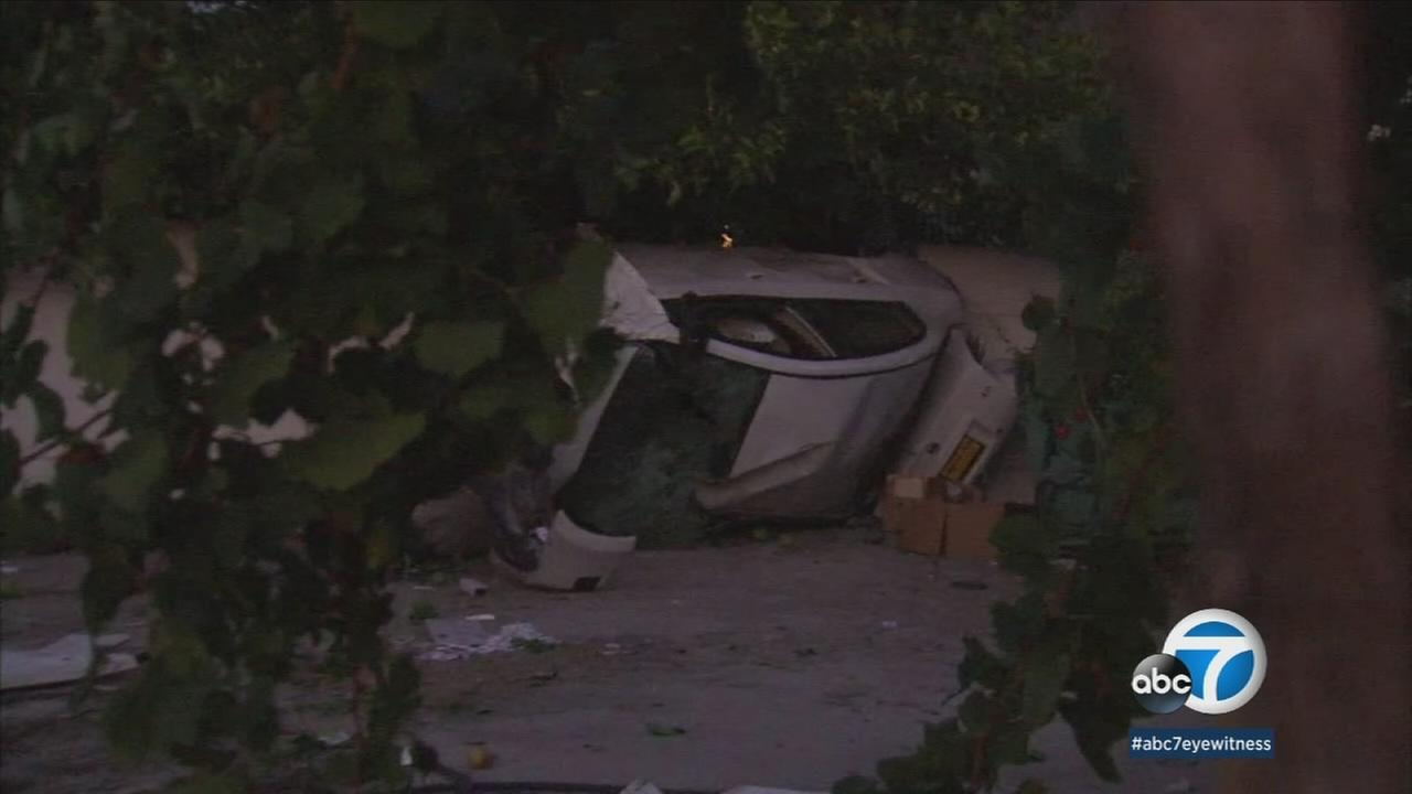 A car is shown upside down in the front yard of a Sun Valley home after a crash in the area.