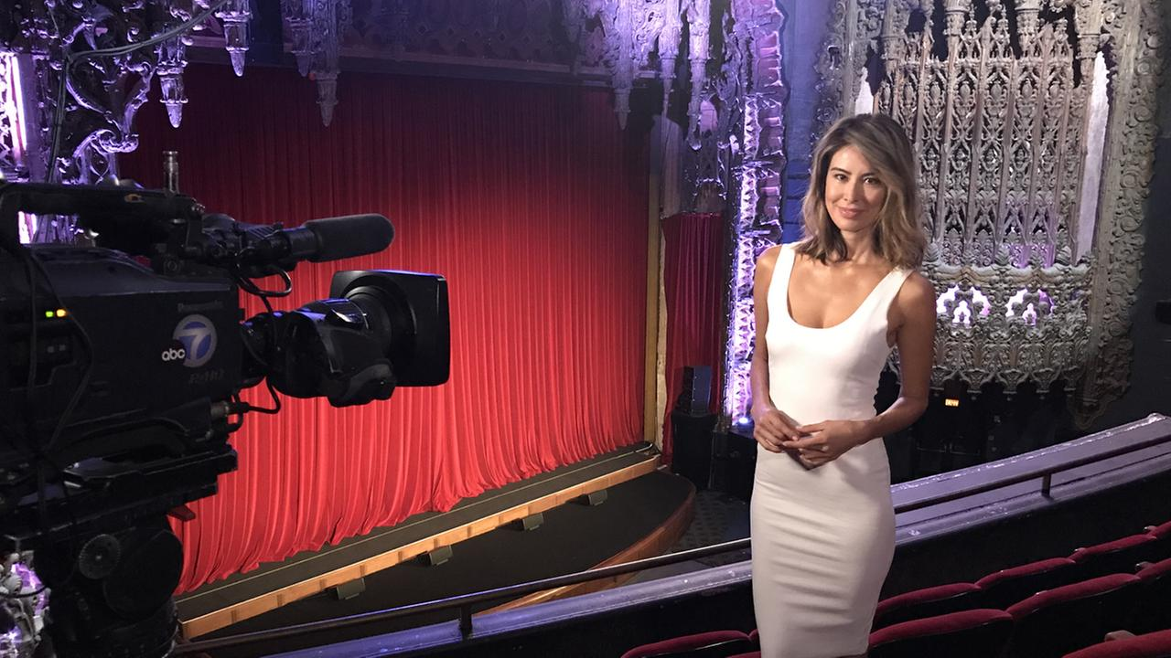 Vista L.A. host Patricia Lopez stands in a theater.