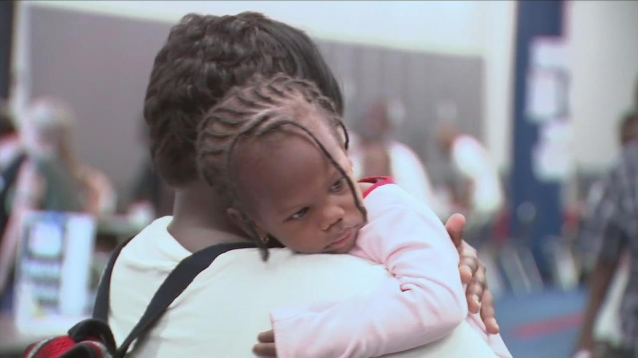 A little girl who was reunited with her mother in a Houston shelter is shown.