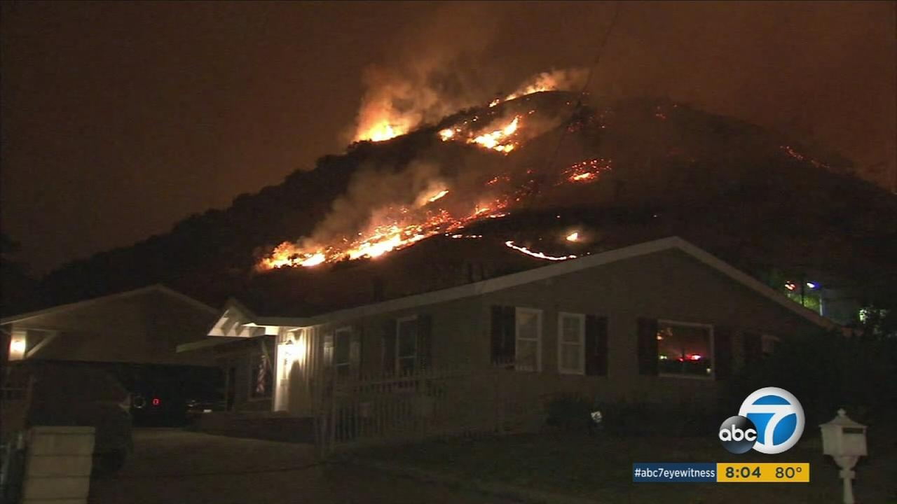 Flames from the La Tuna Fire are seen above a home on Saturday, Sept. 2, 2017.