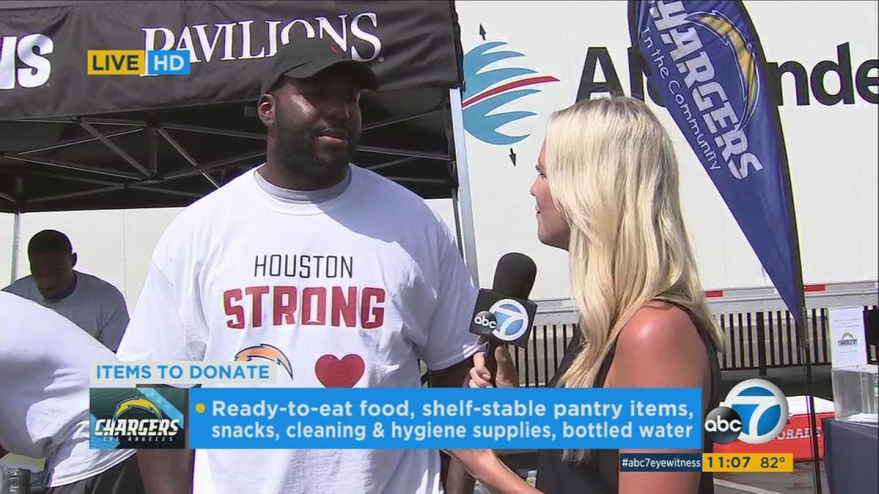 Ashley Brewer talks to a Los Angeles Chargers player as they gather supplies for Hurricane Harvey victims.