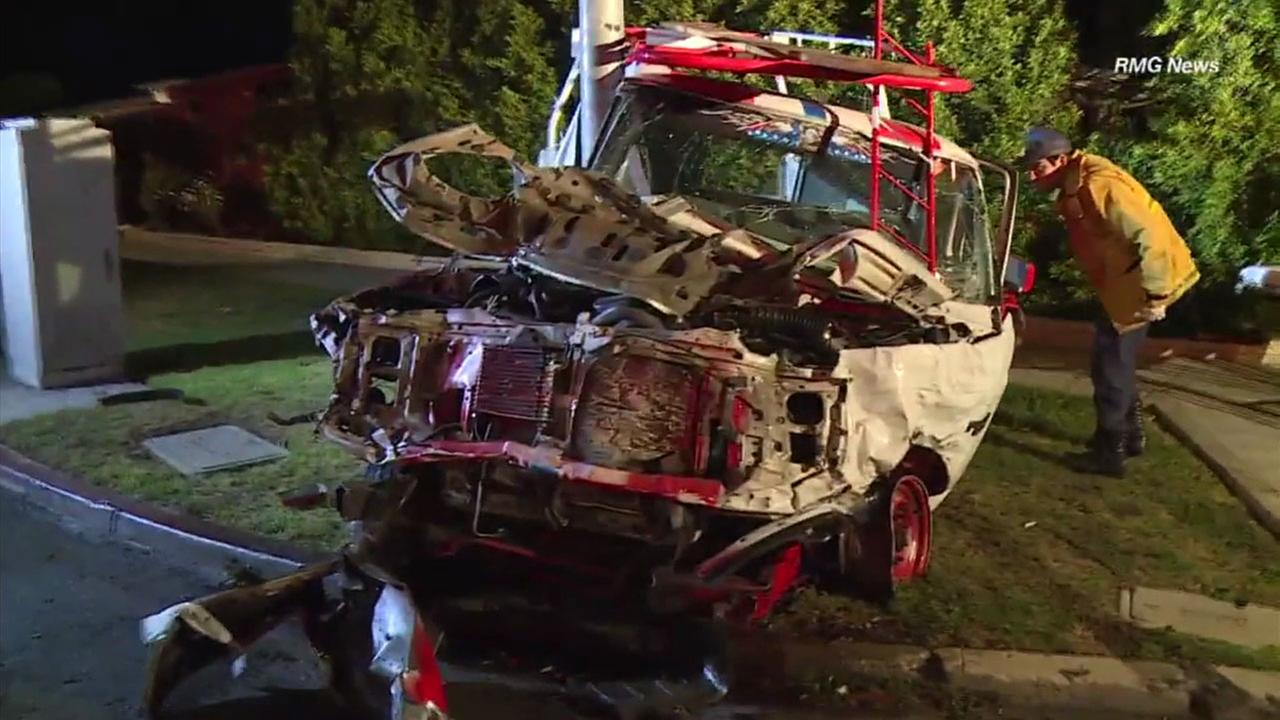 A mangled truck sits at a light pole after a hit-and-run driver was ejected from the vehicle early Wednesday morning in Hancock Park.