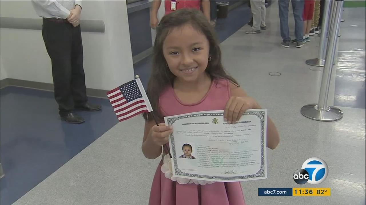 A young girl smiles as she holds up her certificate declaring her a new citizen of the United States.