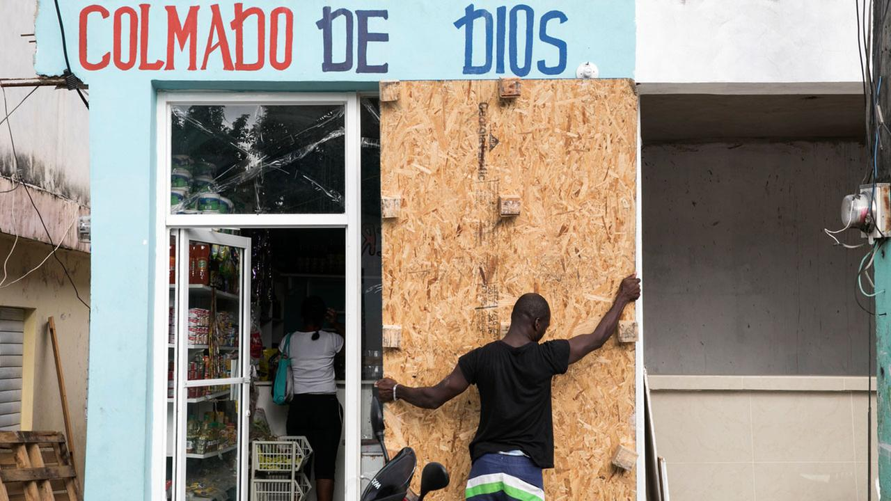 A man covers a bodegas windows before the arrival of Hurricane Irma in Las Terrenas, Dominican Republic, Wednesday, Sept. 6, 2017.