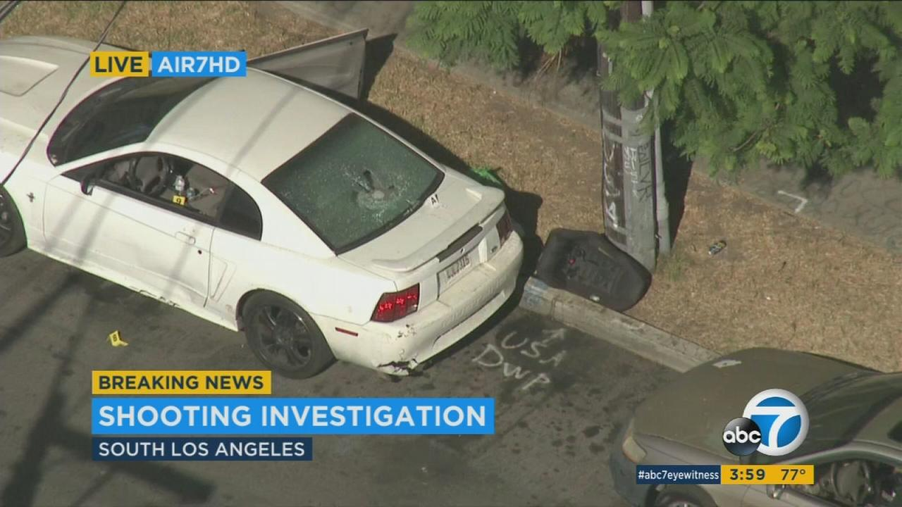 A cars window is blown out, and a car seat sits on a curb following a deadly shooting in South Los Angeles on Tuesday, Sept. 12, 2017.