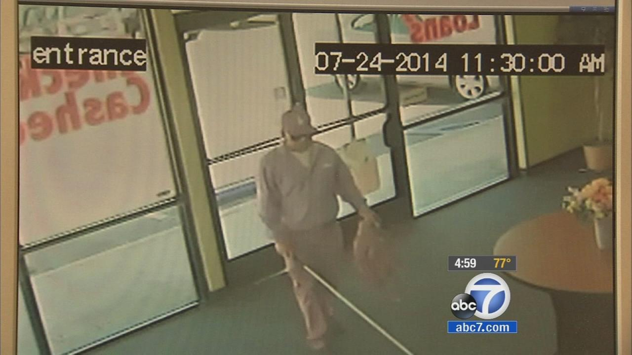 Surveillance video shows a man who robbed a check cashing store by pretending to be blind on July 24, 2014.