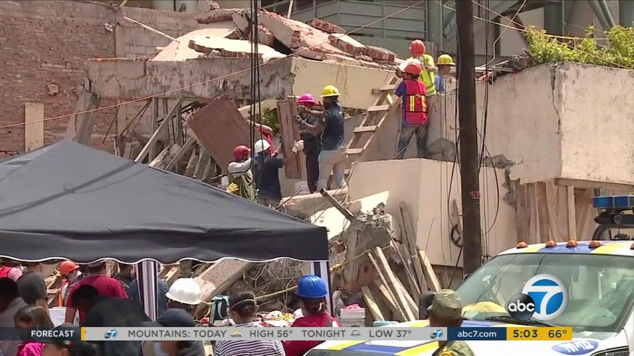 Rescue crews remove debris from a collapsed building in Mexico following a 7.1 earthquake that struck Tuesday, Sept. 19, 2017.