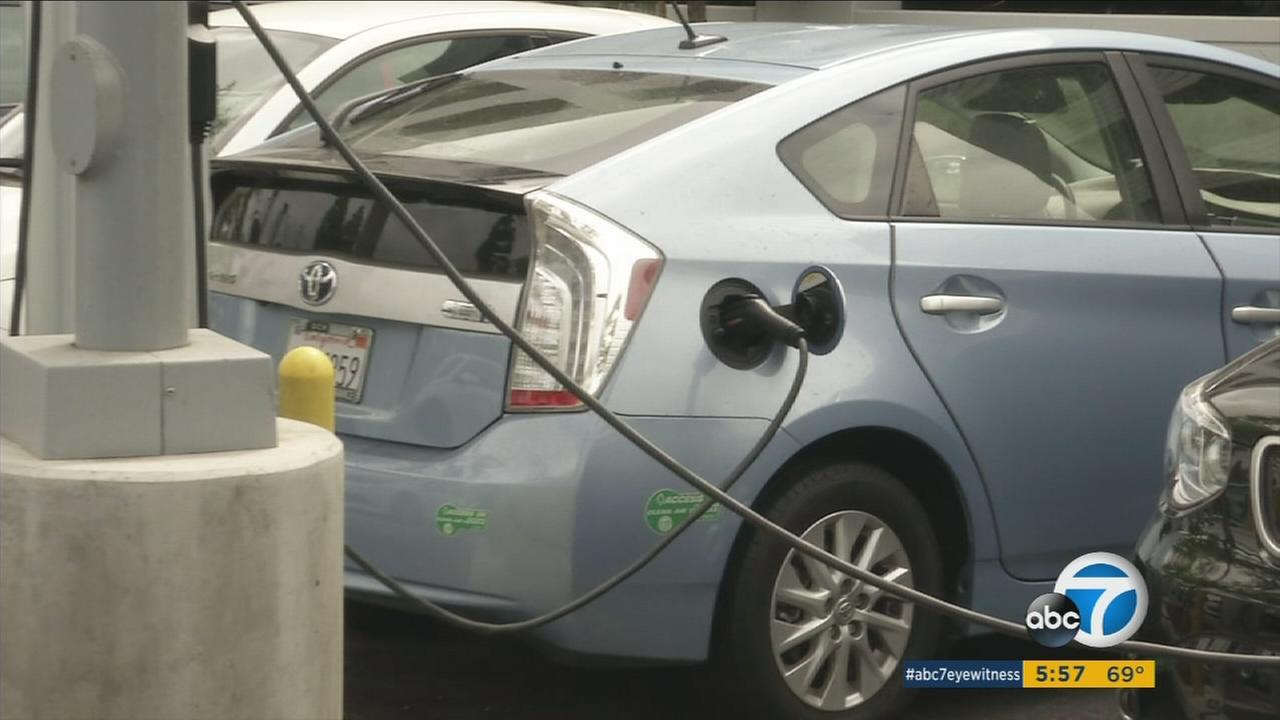 A Prius is shown charging at a station.