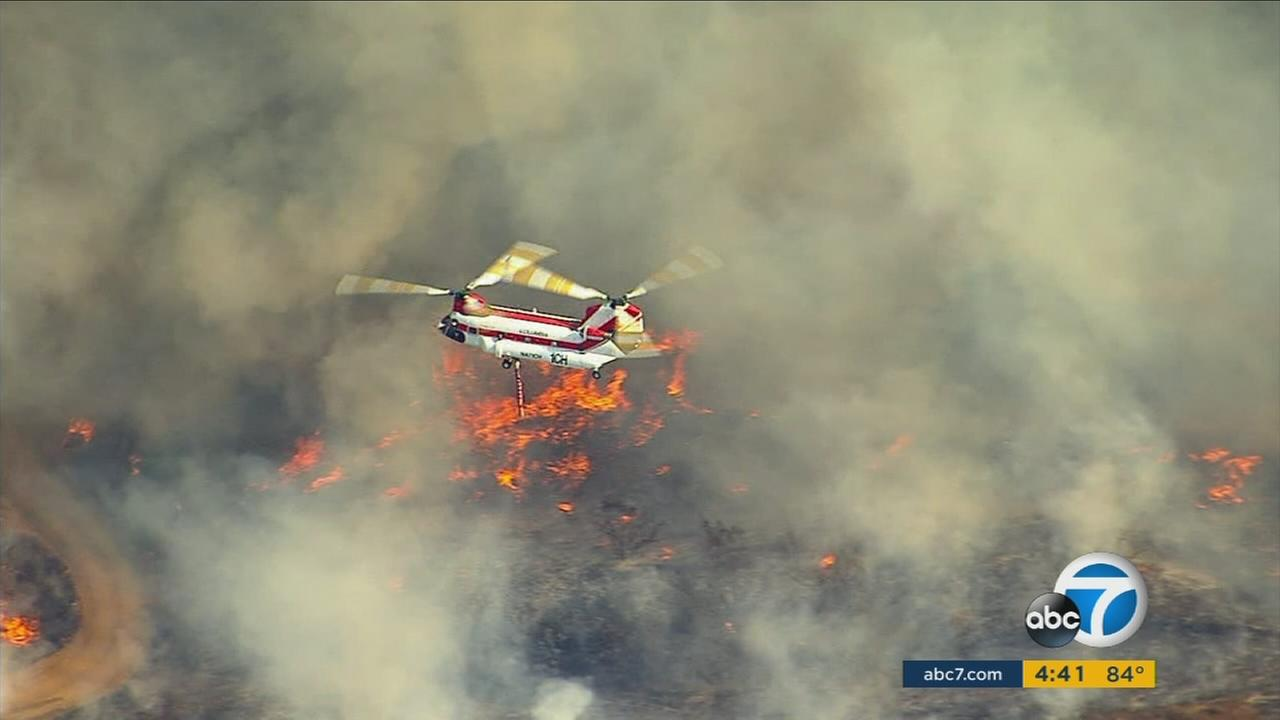 A water helicopter drops over a brush fire burning along the 91 Freeway near the Anaheim-Corona border on Monday, Sept. 25, 2017.