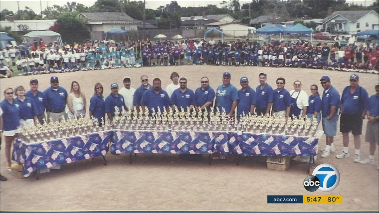 Parents and children in youth baseball and softball leagues are shown with all of their trophies in a group photo.