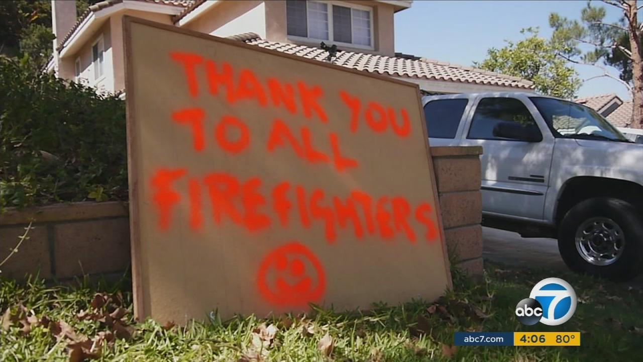 A sign thanking firefighters for saving homes in Corona is shown.