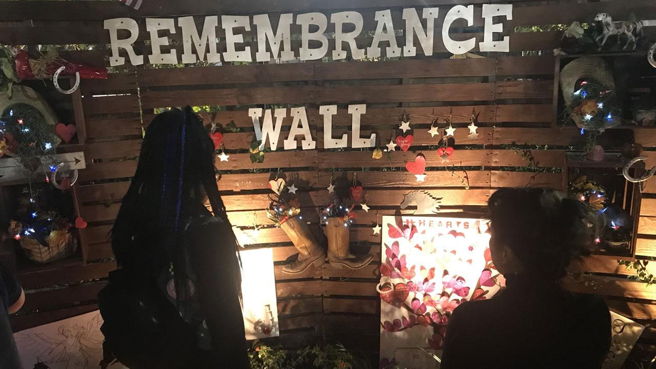 Visitors look at the Remembrance Wall constructed at a healing garden created by volunteers in Las Vegas to honor the mass shooting victims.