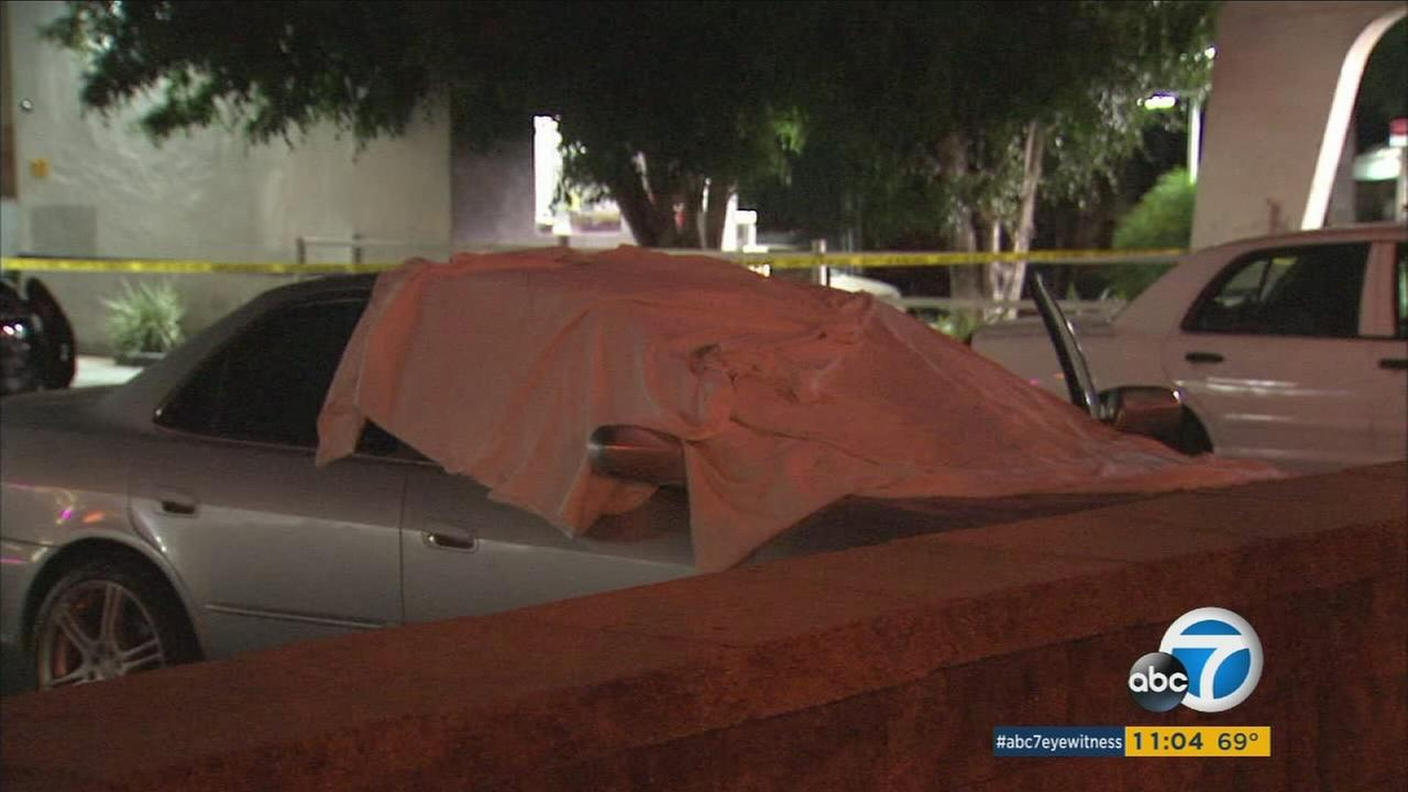 A white sheet covers a car in West Hollywood where a body was discovered on Saturday, Oct. 7, 2017.