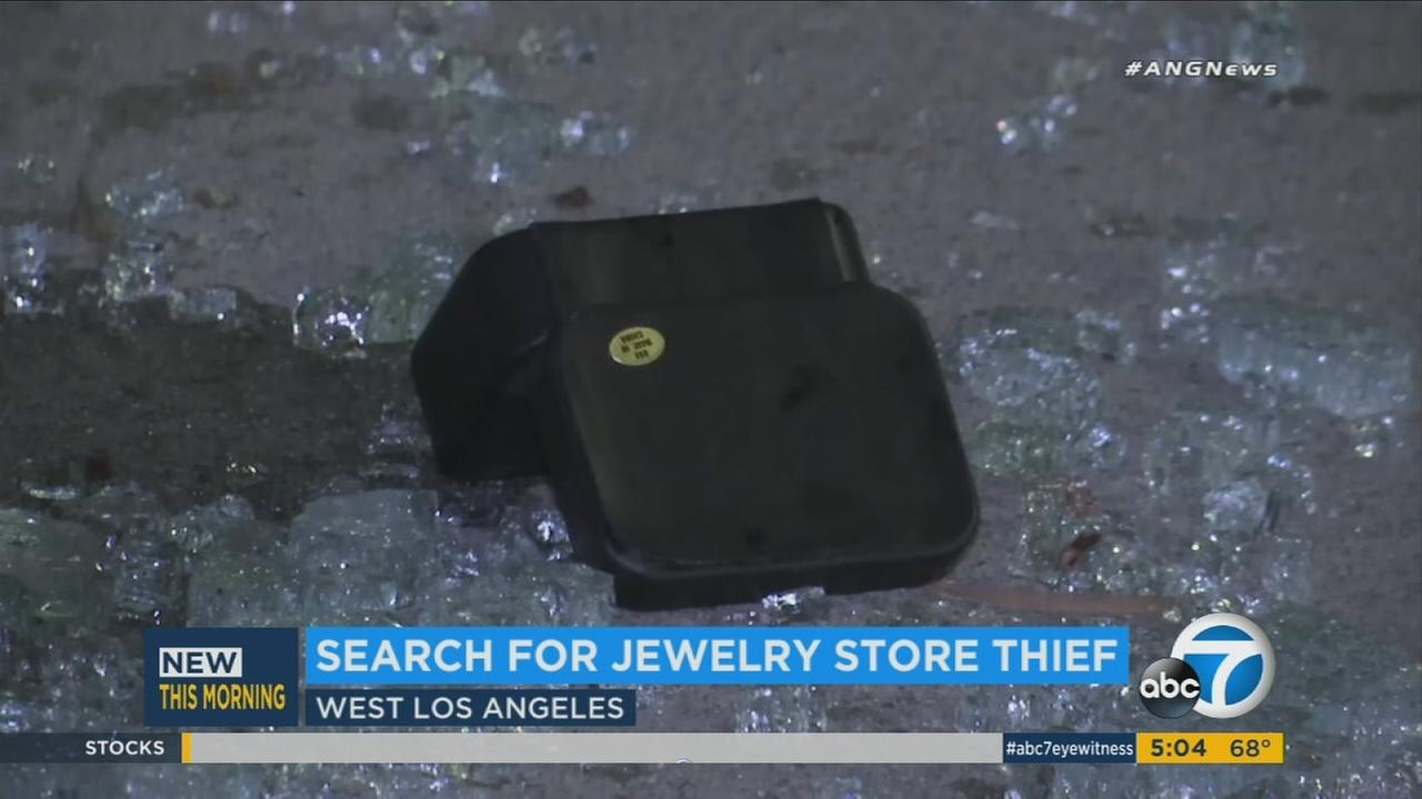 A jewelry container is shown on the ground amid broken glass after a robbery suspect smashed a window at a West Los Angeles business on Sunday, Oct. 8, 2017.