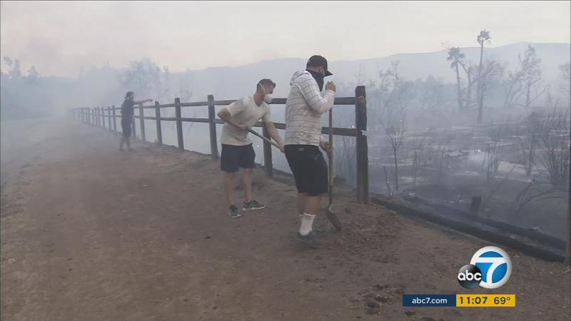 <div class='meta'><div class='origin-logo' data-origin='KABC'></div><span class='caption-text' data-credit='KABC'>Orange County residents volunteer to work the Canyon Fire 2 after it scorched through the Peters Canyon Regional Park on Monday, Oct. 9, 2017.</span></div>