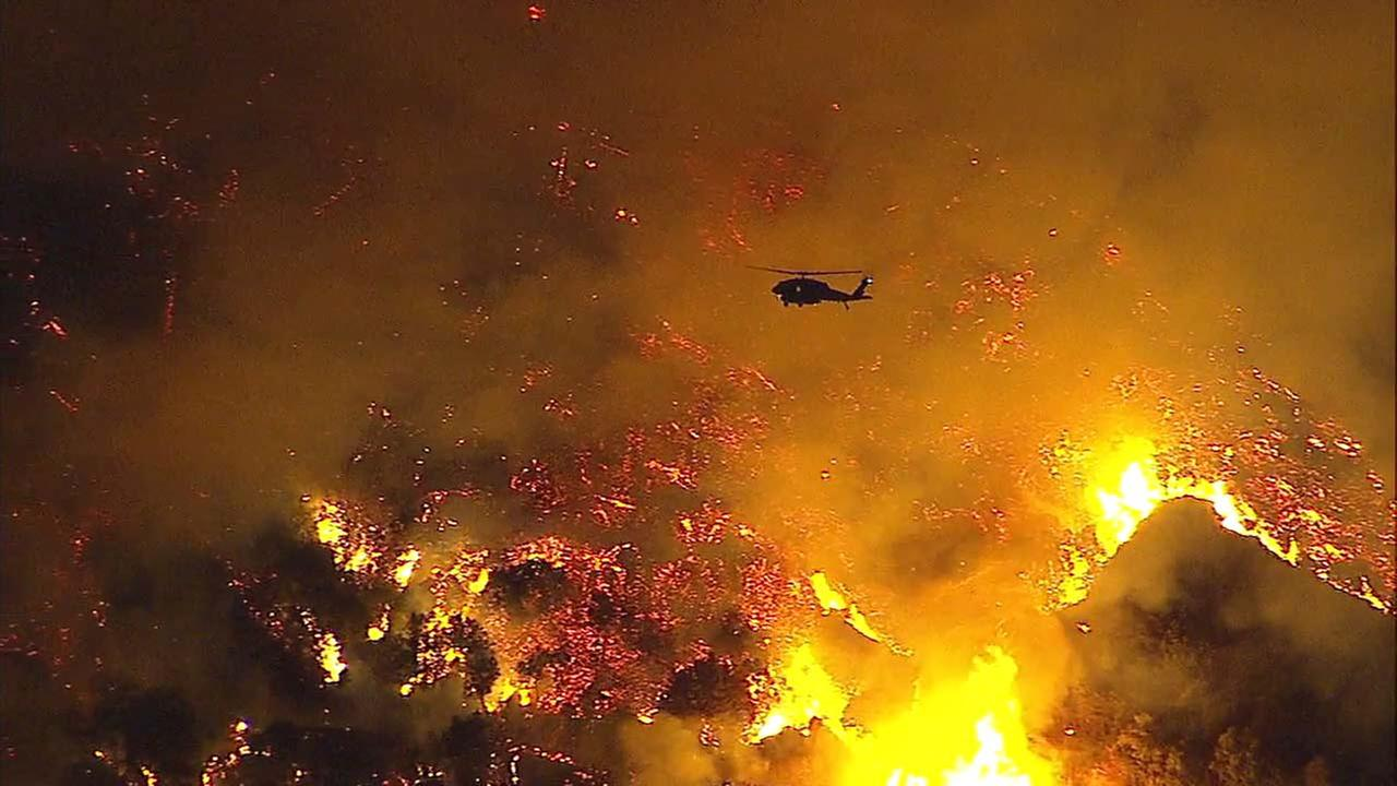 A helicopter is seen flying over a fire on Mount Wilson before executing a water drop on Tuesday, Oct. 17, 2017.