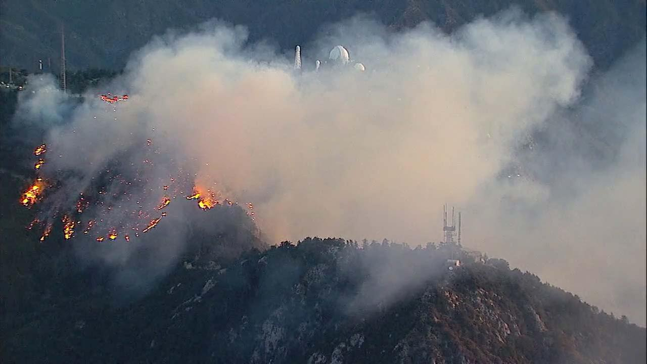 Smoke and flames are seen along the hillsides of Mount Wilson on Tuesday, Oct. 17, 2017.