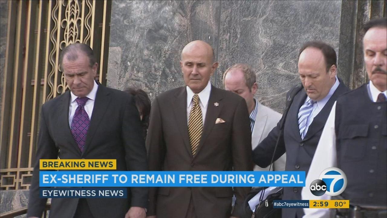 Ex-Sheriff Lee Baca is shown walking out of a court house during his corruption and obstruction trial.