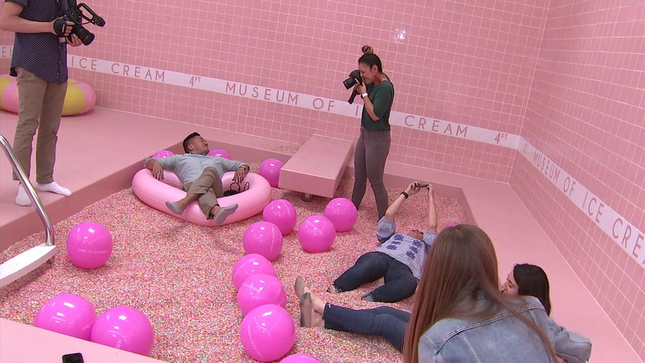 A group of visitors to the Museum of Ice Cream lounge around and take photos in the sprinkle pool.