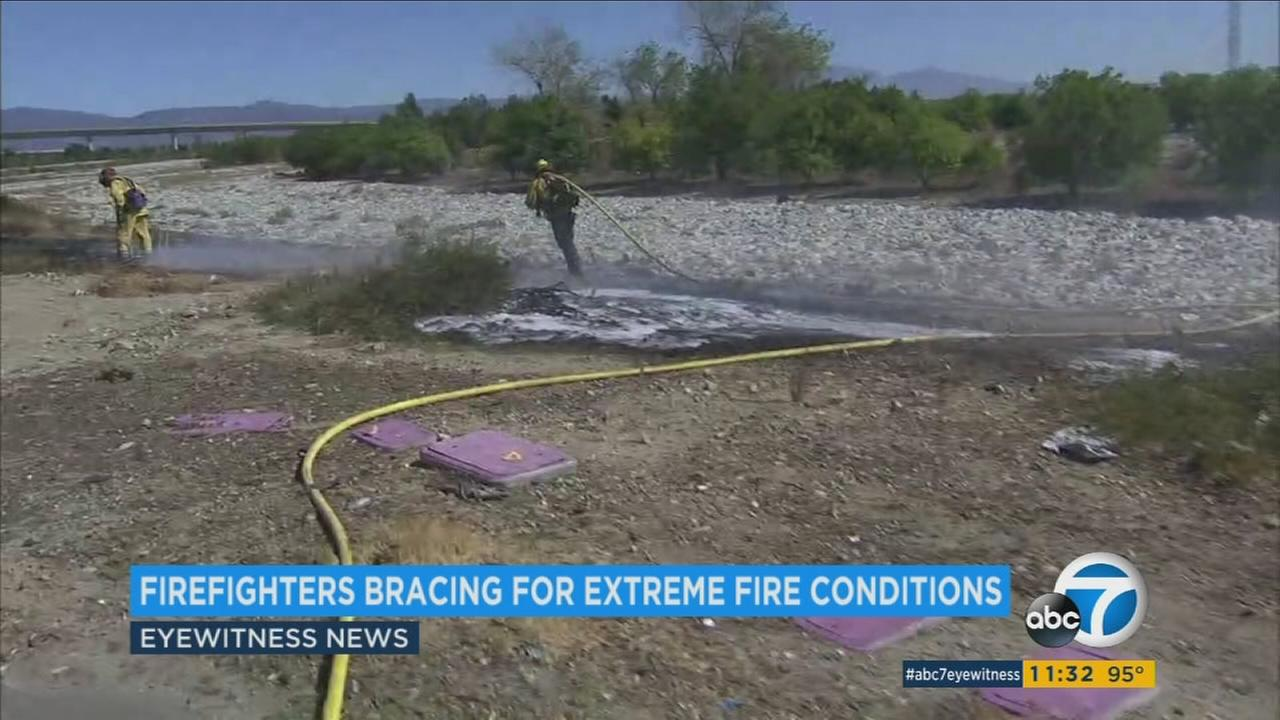 Firefighters are seen dousing hot spots in the Inland Empire.