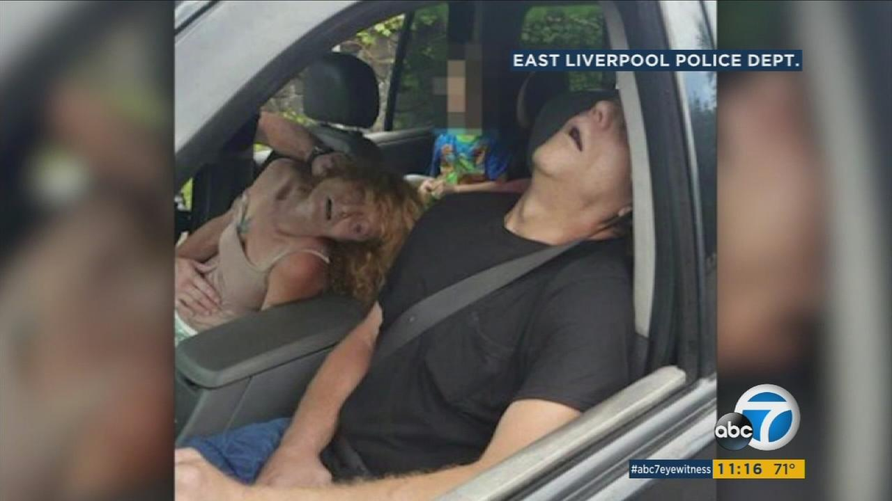 Two people who overdosed on opioids while their children were in the car are shown in a viral photo.