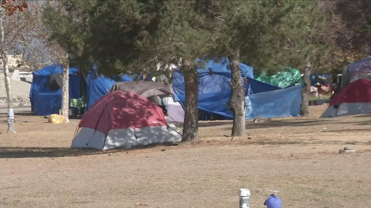 Homeless encampments are shown along the Santa Ana River Trail in a photo.