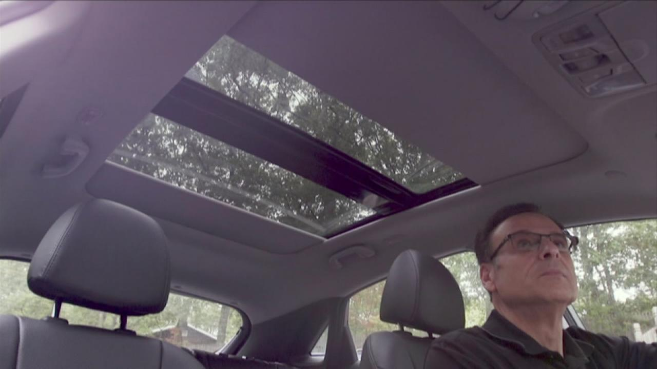 A man looks at a vehicle sunroof in a photo.