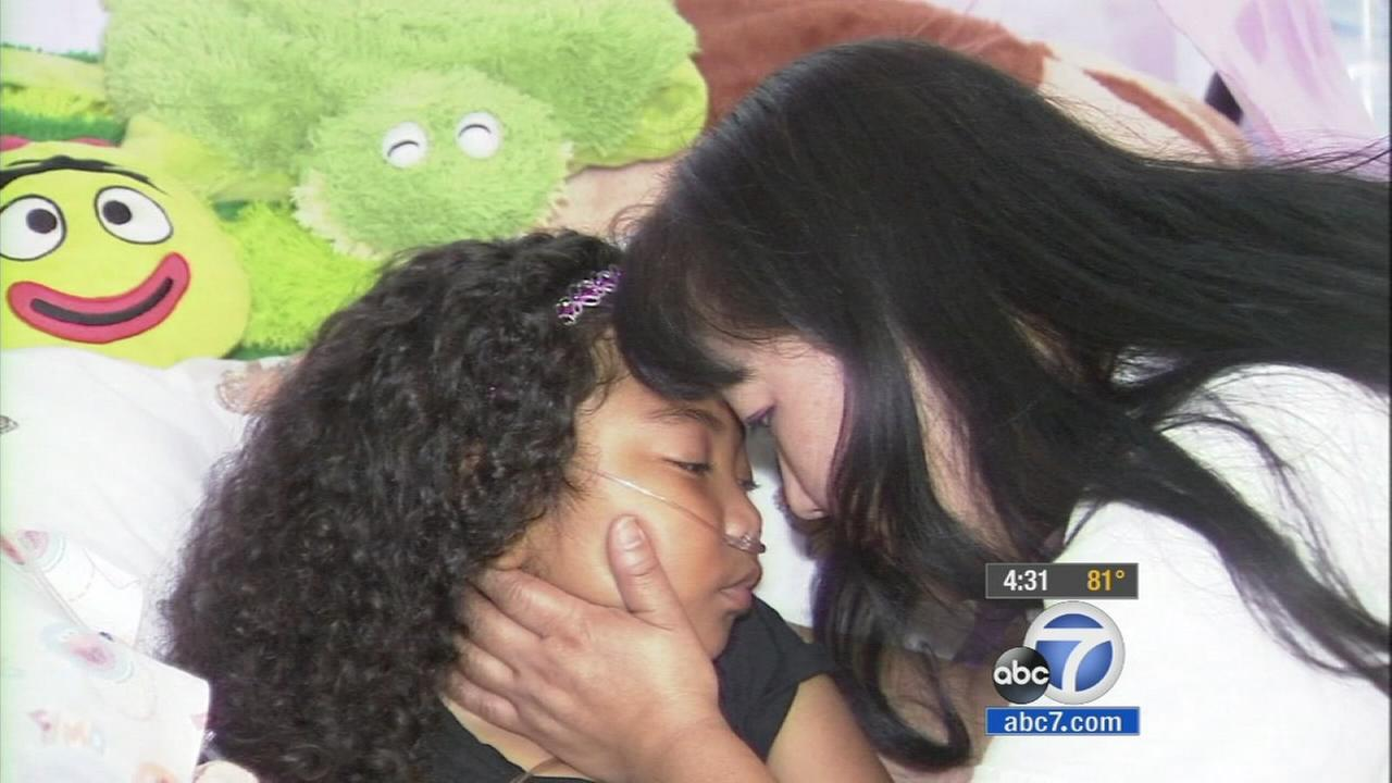 Kim Traer cuddles with her 5-year-old daughter Arwyn, who is terminally ill.